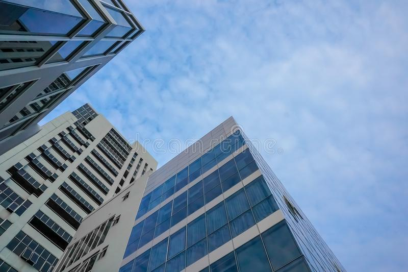 Nedersta sikt av moderna skyskrapor i affärsområde mot blå himmel arkivfoto