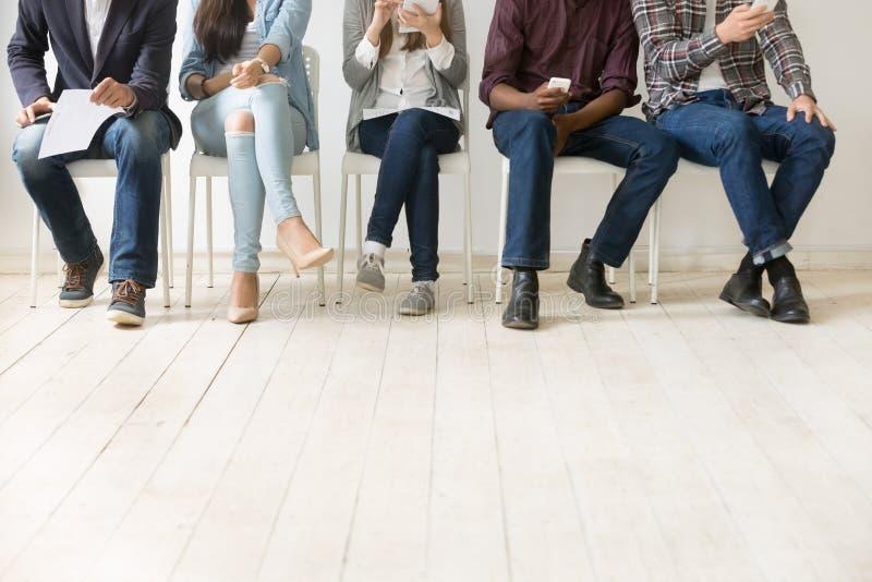 Nedersta sikt av olika arbetskandidater som väntar på jobbintervju royaltyfria bilder