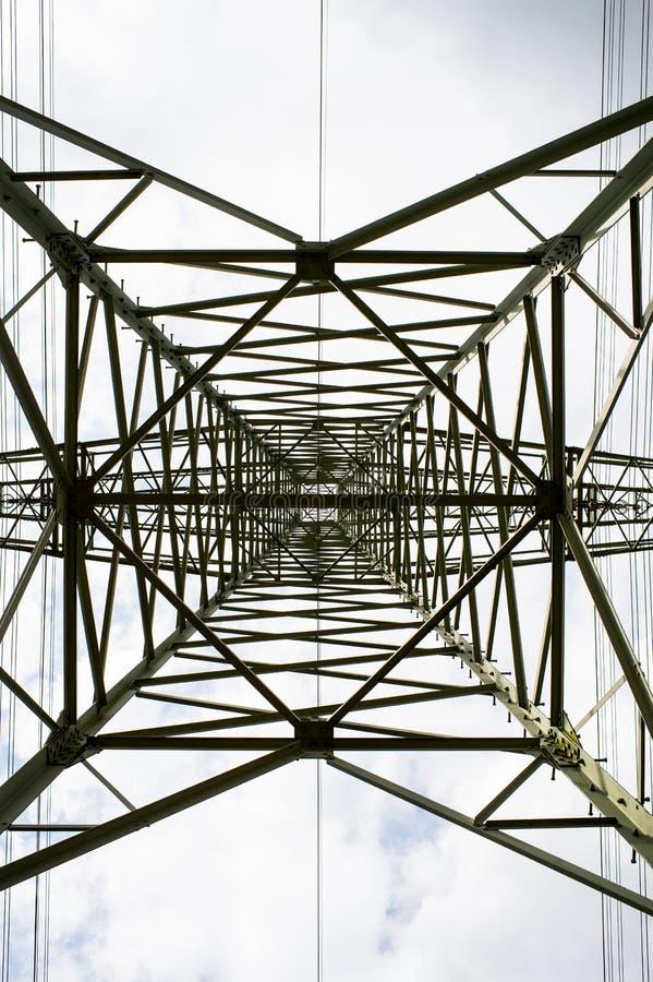Nedersta sikt för överföringstorn Makttorn på molnig himmel Elektricitetspylonstruktur för kraftledning Hög spänningsstolpe royaltyfri fotografi
