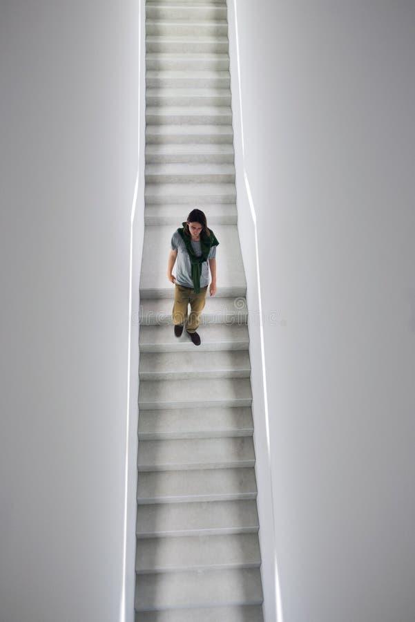 Nedgående trappuppgång för man i det vita kubgallerit royaltyfri bild