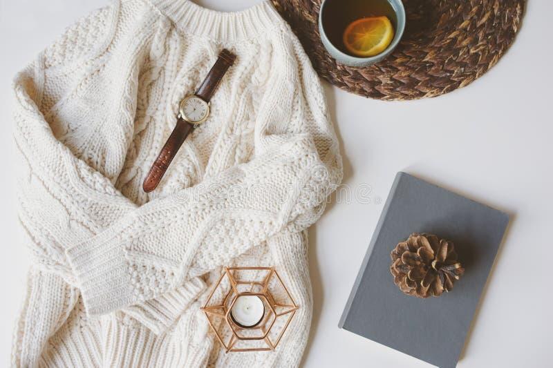 Nedgång eller hemtrevlig stillebenuppsättning för vinter Värme den stack tröjan, kopp te med citronen, och boken med sörjer kotte arkivfoton