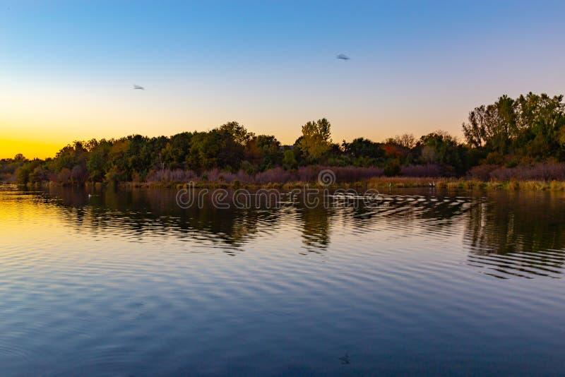 Nedgången färgar på skymning med krusningar på sjön royaltyfria foton