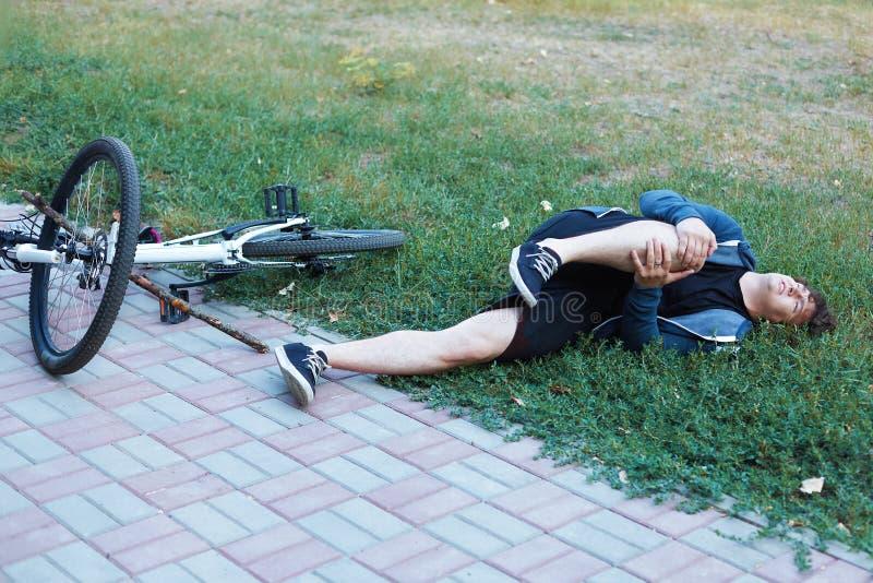 Nedgången från cykeln i naturligt parkerar Den unga caucasian mannen avverkar av cykeln på jordningen Olycka med en pinne i ett h arkivbild