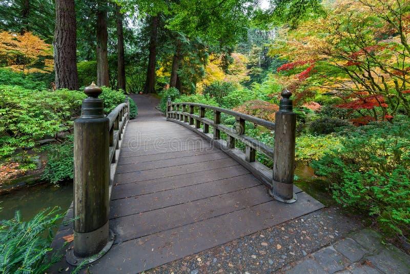 Nedgångfärger vid fotbron i japanträdgård fotografering för bildbyråer
