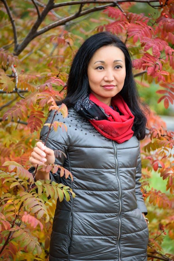 Nedgångkvinna som ler - höststående av den lyckliga älskvärda och härliga asiatiska Caucasian unga kvinnan för blandat lopp i sko royaltyfri foto
