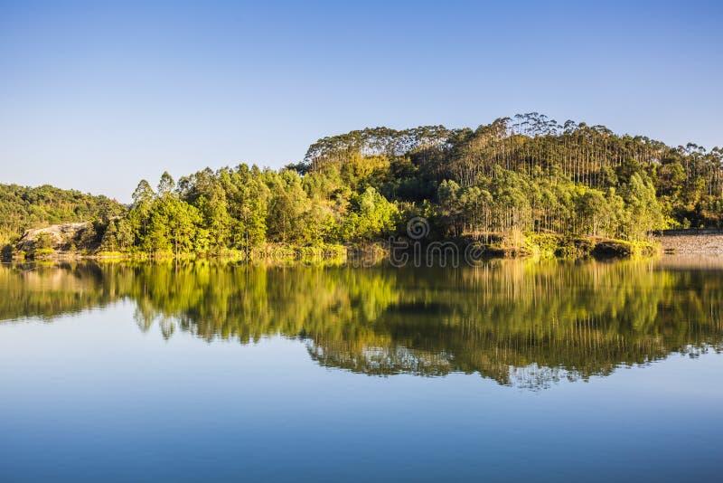 Nedgångplats med Autumn Trees Reflection i sjön royaltyfri foto