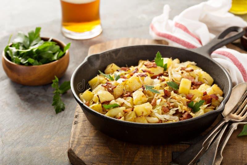 Nedgångsidomaträtt med stekt kål, potatisar och bacon royaltyfria bilder