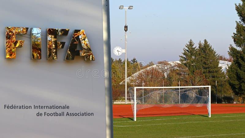 Nedgångträdreflexioner i det FIFA ingångstecknet på Zurich förlägger högkvarter med fotbollfältet och mål fotografering för bildbyråer