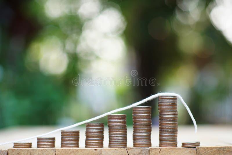 Nedgångtrenddiagram av fastigheten som framläggas av myntbuntar och tangenten med huskeyringen, finansiell presentation, affärsid arkivfoto