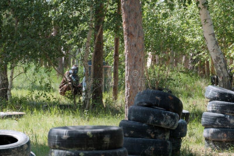 Nedgrävning av sopor i skogen för en laglek i paintball En tonåring som bär en svart skyddande maskering och kamouflagekläder med fotografering för bildbyråer