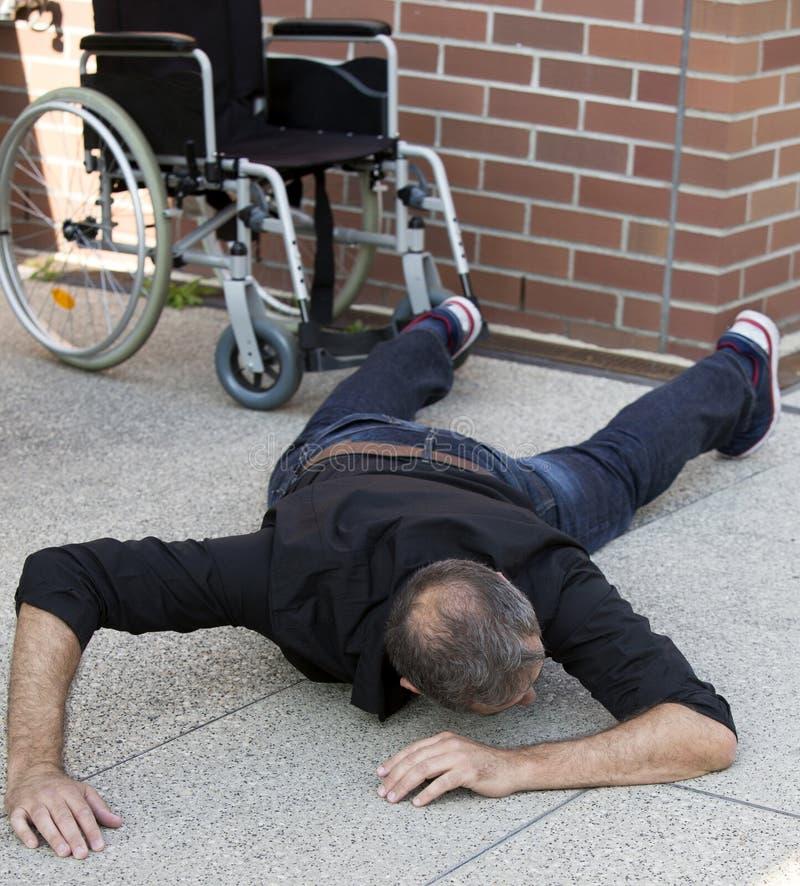 Nedsatt man på golvet, når att ha fallit ut ur rullstolen arkivfoton