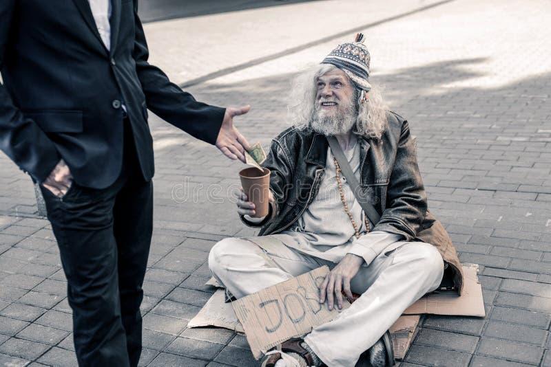 Nedsmutsad grå färg-haired fattig man som är arbetslös och bor på gatan arkivfoto