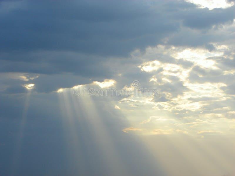Nedstigning av gudomliga välsignelser från himmel - solstrålar till och med moln royaltyfri foto