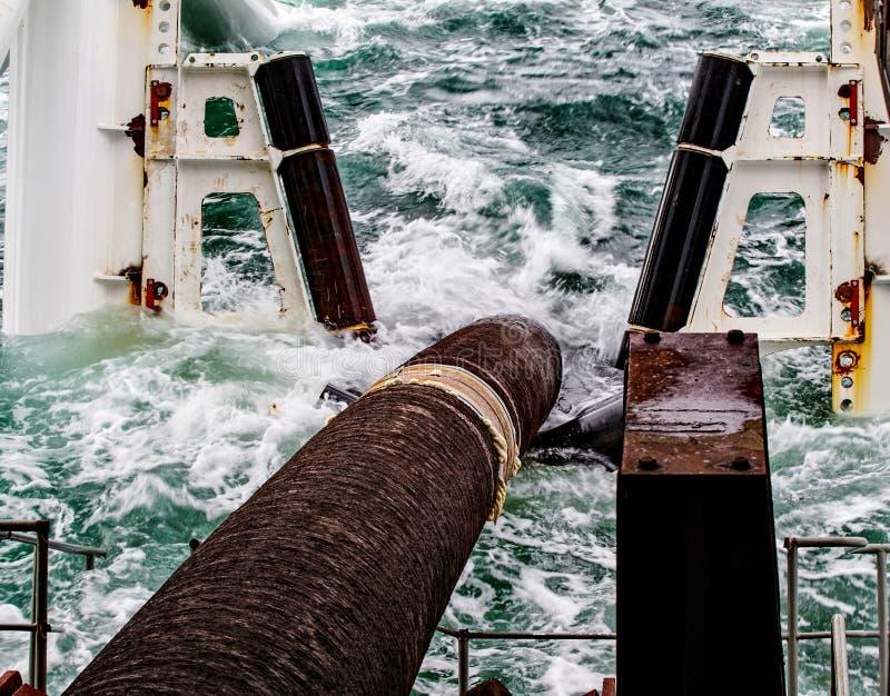 Nedstigning av rörledningen till en botten som evakuerar med pipelayingpråm Installation av den undervattens- gasledningen royaltyfri fotografi