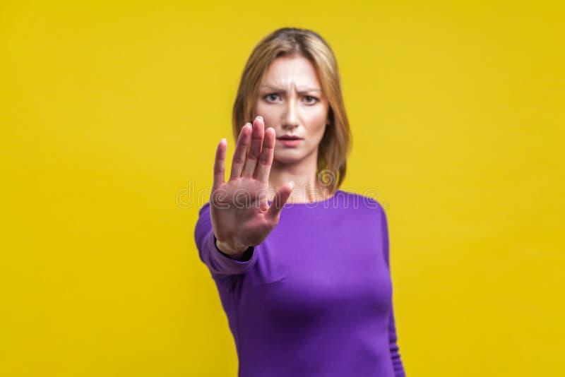 Nee, verboden! Portret van overstuur jonge vrouw met stopgebaar geïsoleerd op gele achtergrond royalty-vrije stock foto's