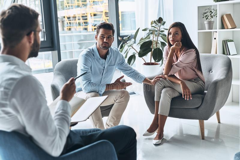 They need an advice. Young married couple talking while sitting on the therapy session with psychologist stock photo