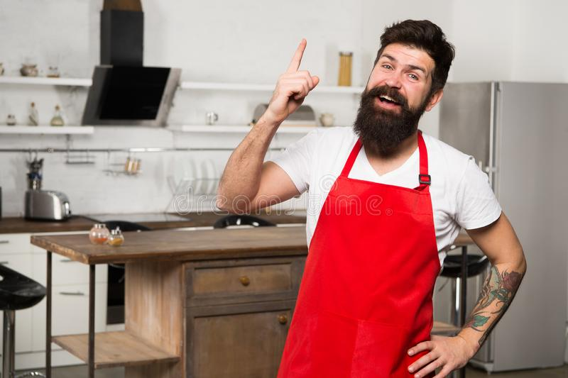 Need culinary inspiration. How to turn cooking at home into habit. Man bearded hipster red apron stand in kitchen. Kitchen furniture store. Cooking in new stock photography