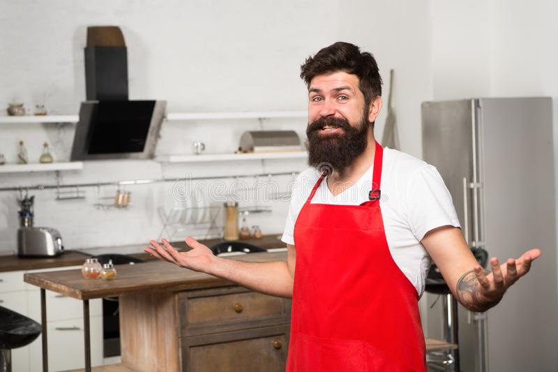 Need culinary inspiration. Weekend begins from tasty breakfast. How to turn cooking at home into habit. Man bearded. Hipster red apron stand in kitchen. Kitchen stock photography