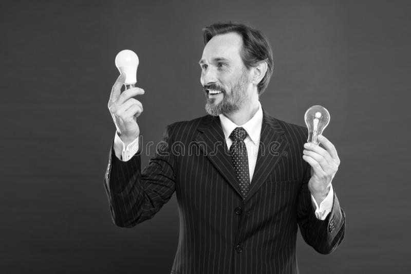 Need fresh ideas. Electricity and energy. Businessman in suit hold light bulb. Man with beard search for inspiration. Lamp. Mature bearded man with lamp. Power stock photography