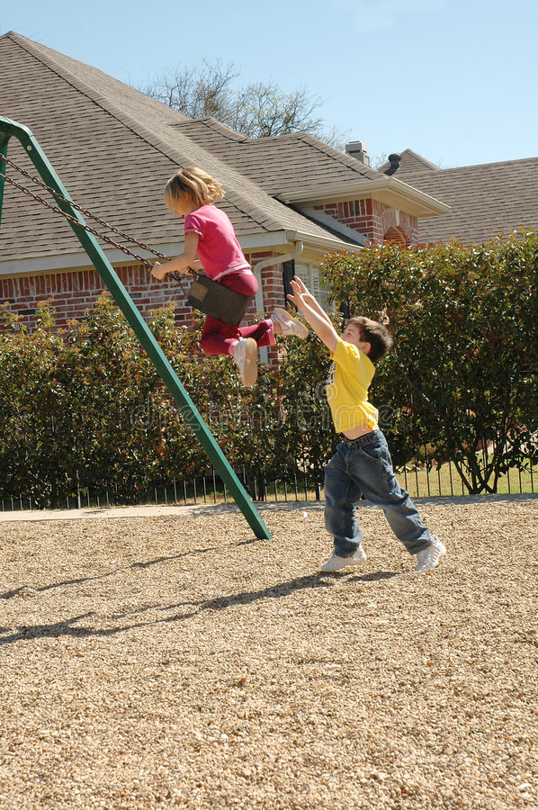 Need a hand. Little boy pushes girl on swing. Playground safety stock photo