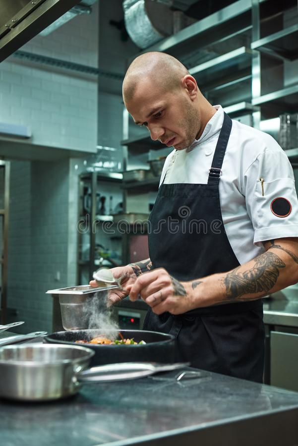 Need more spices. Vertical photo of restaurant chef with several tattoos adding a special spice to fresh cooked pasta royalty free stock photos