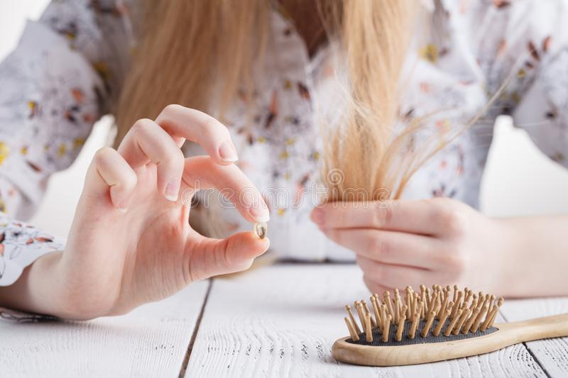 Need more vitamins, Woman with hair problems, lost hair on comb royalty free stock image