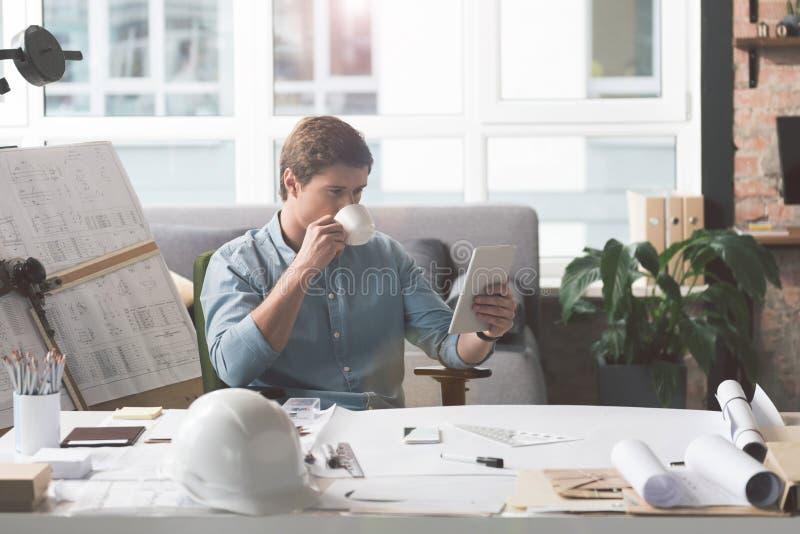 Skillful youthful architect enjoying fresh espresso royalty free stock photos