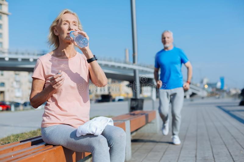 Athletic woman drinking water after a morning run stock photography