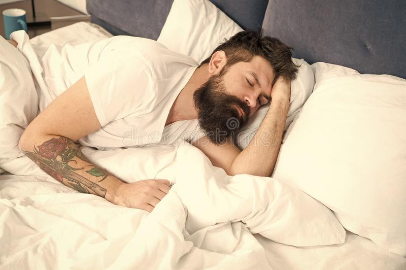Need some rest. Sleep disorders concept. Man bearded hipster having problems with sleep. Guy lying in bed try to relax. And fall asleep. Relaxation techniques stock photography