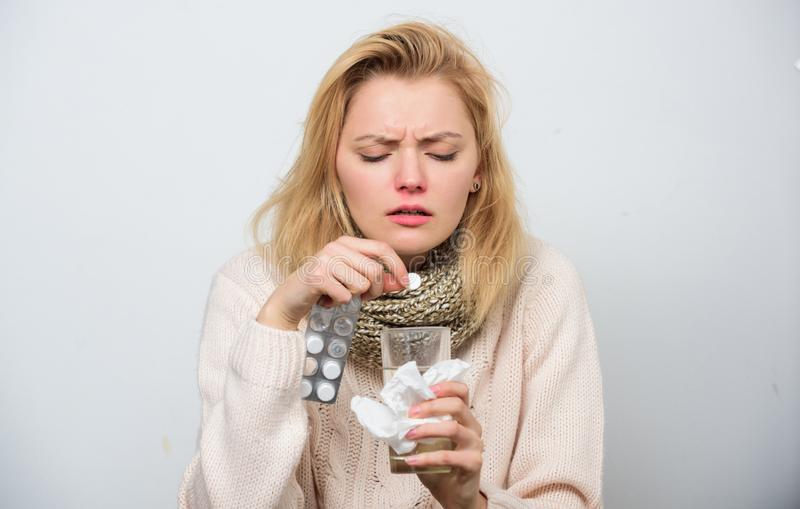 Need some vitamins. Ill woman treating symptoms caused by cold or flu. Unhealthy woman holding pills and water glass. Cute sick girl taking anti cold pills royalty free stock photos