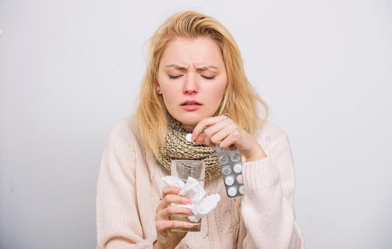 Need some vitamins. Ill woman treating symptoms caused by cold or flu. Unhealthy woman holding pills and water glass. Cute sick girl taking anti cold pills royalty free stock photography