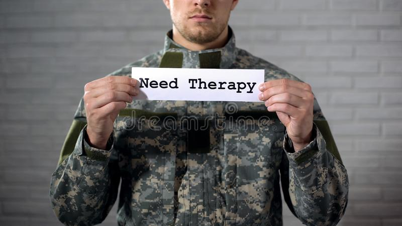 Need therapy word written on sign in hands of male soldier, medical help. Stock photo stock images
