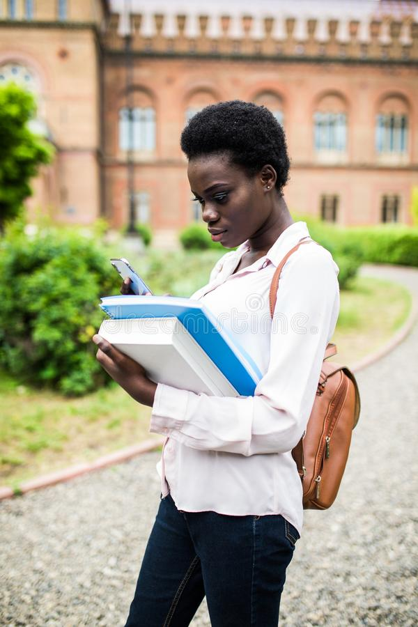 Need to check some information in Internet. Happy young african american uni student using cell phone stock photography