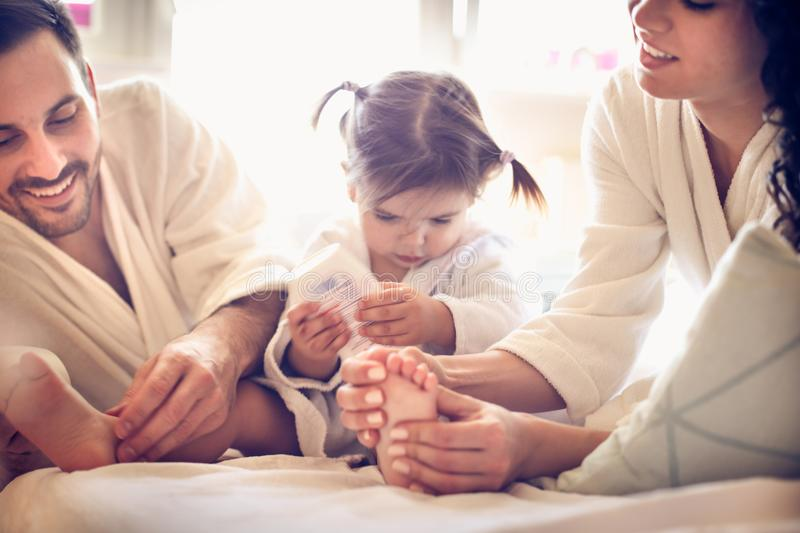 We need to massage feet to our little girl. Happy young parents. stock images