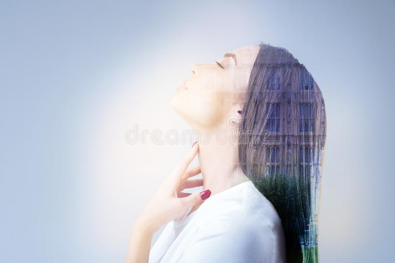 Frustrated brunette girl raising her head. Need to relax. Charming female person touching her neck and keeping eyes closed while standing against urban stock photo
