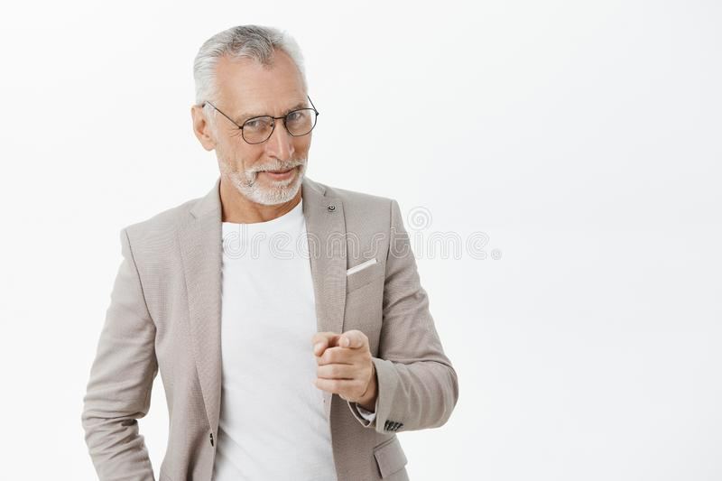 We need you man. Portrait of happy amused and tricky mature macho businessman in glasses and suit smiling looking and stock images