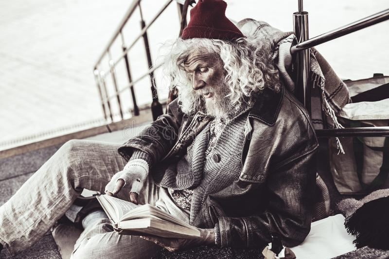 Old dirty loafer reading book that passerby giving him. stock photo