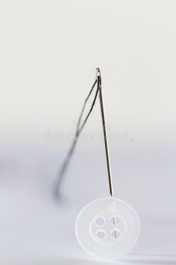Needle, button and string. A single sew needle with a string on it. Small white button in front stock photography
