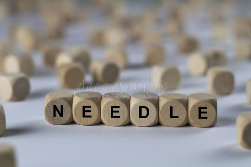 Needle - cube with letters, sign with wooden cubes. Series of images: cube with letters, sign with wooden cubes stock photography