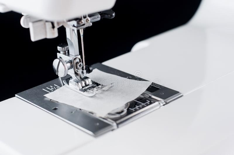 Needle Electromechanical white sewing machine close up on a black background, isolate stock photography