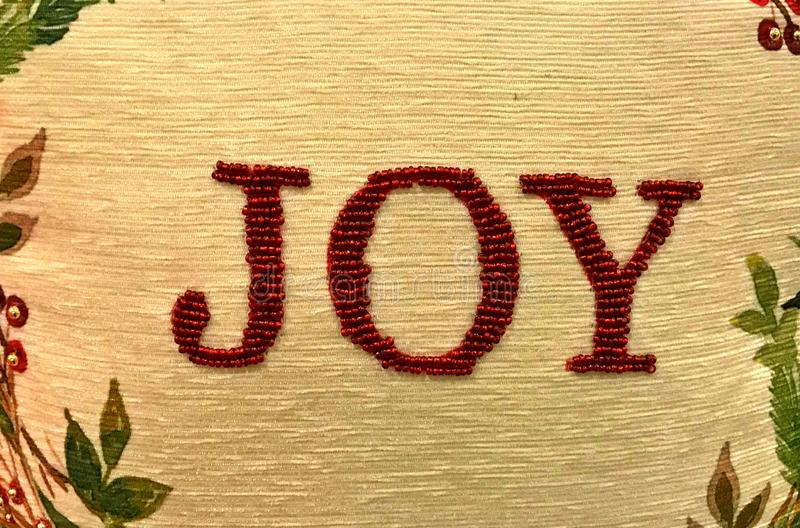 Needle-point embroidery of the word JOY. Framed by leaves stock image