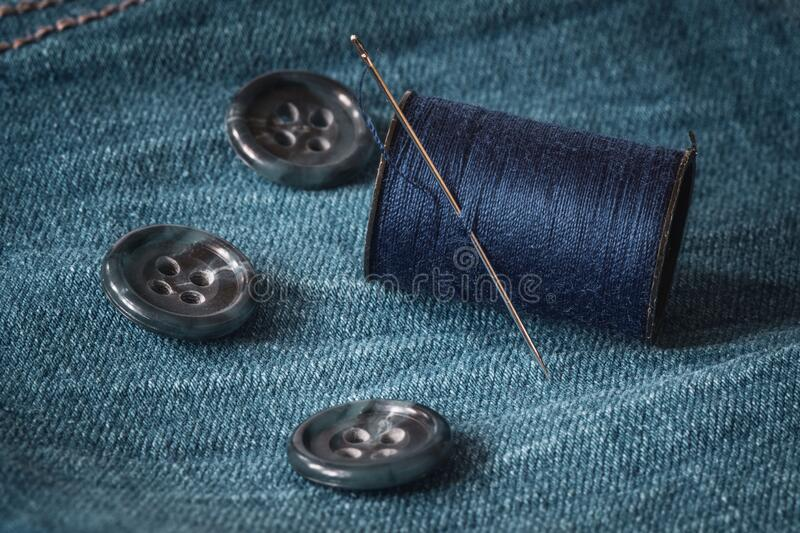 Needle and spool of thread on jeans fabric stock image
