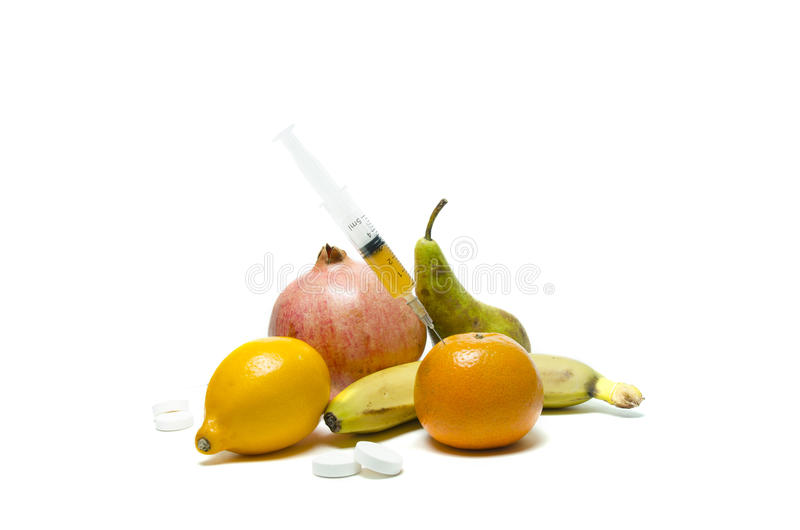 Needle and syringe injected in the fruit. Healthy life versus unhealthy life. Fruits and pills on the table. stock photos