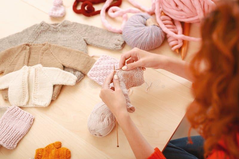 Needlewoman che lavora alla raccolta tricottata del bambino fotografia stock libera da diritti