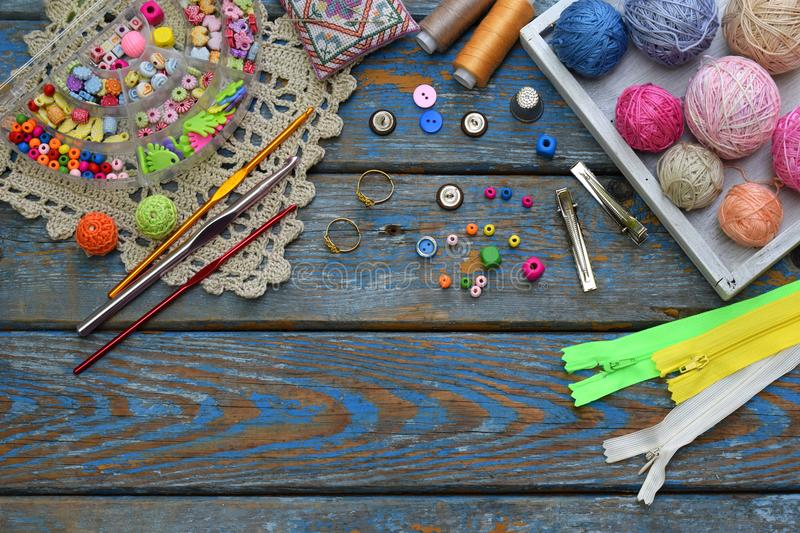 Needlework accessories for creating crocheted jewelry. Beads, threads, hooks, buttons on wooden background. Knitting, crochet, emb. Roidery, sewing Small stock photos
