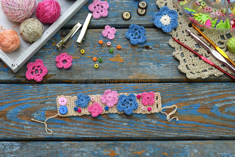 Needlework accessories for creating crocheted jewelry. Step 2 - sew crocheted flowers to bracelet or chain. DIY project. Small bus. Iness. Income from hobby stock photography
