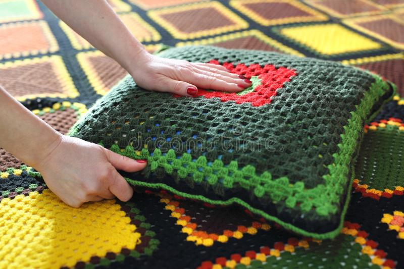 Needlework. Colorful woolen pillow and bedspread crocheted royalty free stock photography