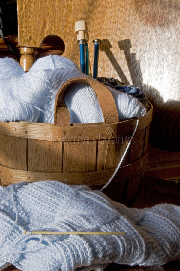 Needlework Crafts. A partially completed crochet baby blanket and a basket of yarn and knitting needles rests on the seat of an old oak rocker stock photos