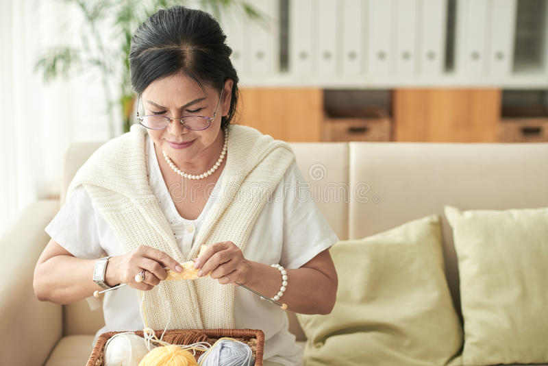 Needlework. Pretty elderly woman busy with knitting at home royalty free stock image