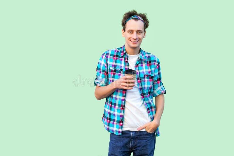 Neem een koffiepauze Knappe jonge volwassen hipstermens in witte t-shirt en geruite het document van de overhemds bevindende hold stock foto